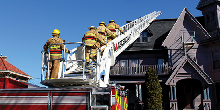 Ladder from truck with firefighters going onto roof